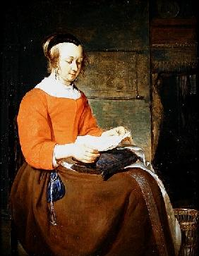 A young woman seated in an interior, reading a letter