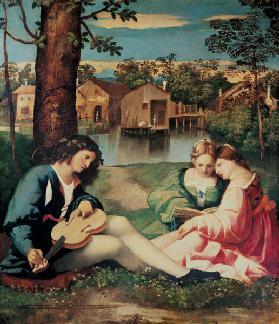 Youth with a guitar and two girls sitting on a river bank