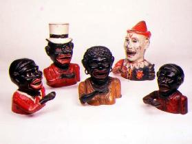 Group of Mechanical cast iron money banks. Left to right: Jolly Nigger with Butterfly Tie, Jolly Nig
