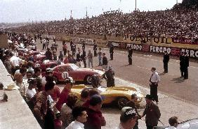 Le Mans racing circuit, France. The cars are lined up in the pits, with the spectator stands opposit